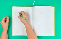 Female hand holding pen, near  blank open notebook in a cell. Green background, top view stock photography