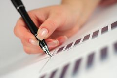 Female hand holding pen over business graph Royalty Free Stock Images