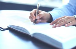 Female hand holding pen ready to make note in opened notebook sheet. Female hand holding pen ready to make note in opened notebook sheet Royalty Free Stock Photo