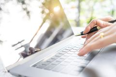 Female hand holding pen typing on laptop key board on table with stock image