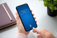 Female hand holding phone with app personal assistant on screen. Female hand holding touch phone with app personal assistant on screen above the table in the royalty free stock photo