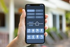 Female hand holding phone with app smart home on screen Stock Images