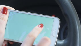 Female hand holding a phone with interface navigator on a screen. Woman using navigatiom system on the phone in car stock video