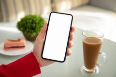 Female hand holding phone with isolated screen in a cafe stock image