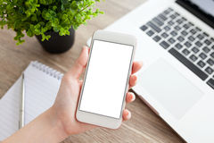 Female hand holding a phone with isolated screen and laptop Royalty Free Stock Photography