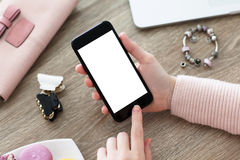 Female hand holding phone with isolated screen on table Stock Image