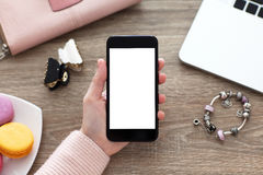 Female hand holding phone isolated screen on table with jewelry. Female hand holding the phone isolated screen on table with jewelry royalty free stock images