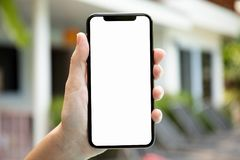 Female hand holding phone with screen on background hou. Female hand holding phone with screen on background of the house royalty free stock image