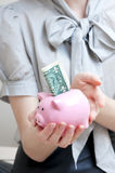 Female hand holding piggy bank containing one dollar. Royalty Free Stock Images