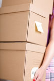 Female hand holding pile of brown cardboard boxes Stock Photography