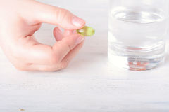 Female hand holding a pill. Close-up of female hand holding a pill. Healthcare concept Stock Photo