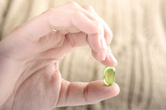 Female hand holding a pill. Close-up of female hand holding a pill. Healthcare concept Royalty Free Stock Image