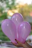 A female hand holding pink baloons Royalty Free Stock Image