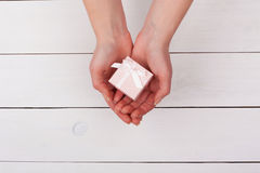 Female hand holding pink gift in hands on a white wooden table. Stock Image