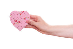 Female hand is holding a pink heart Royalty Free Stock Images