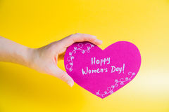 Female hand holding pink paper heart on golden background - Happy Women`s Day Royalty Free Stock Photo