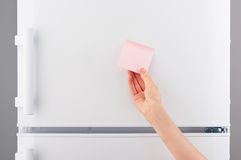 Female hand holding pink paper note on white refrigerator Royalty Free Stock Image