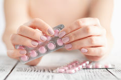 Female Hand holding a pink pill. Closeup view Royalty Free Stock Photos