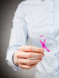Female Hand Holding a Pink Ribbon Royalty Free Stock Photography