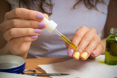 Female hand holding a pipette with oil. A young girl sits at a table and gets a yellow oil on the nails. On the table are nail clippers, a bottle of oil, a jar Stock Image