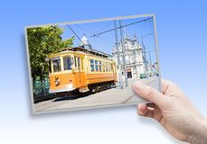 A female hand holding an postcard about the historical trasportation of Porto - on background the `Igreja do Carmo e Carmelitas` stock image
