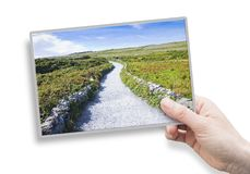 A female hand holding an postcard about a typical Irish flat lan Stock Photo