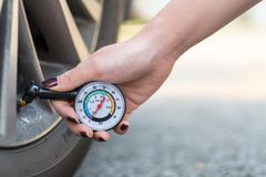 Close up hand holding a pressure gauge measuring a car tyre pressure. Female hand holding a pressure gauge for measure car tyre pressure Royalty Free Stock Photography