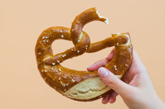 Female hand holding a pretzel Royalty Free Stock Images