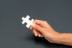 Female hand holding puzzle piece. Royalty Free Stock Photos