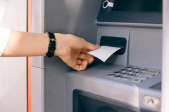 Female hand holding a receipt obtained from the ATM after withdrawing cash Royalty Free Stock Photography