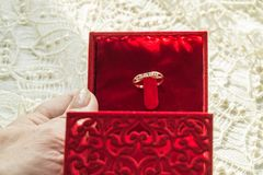 Female hand holding a red box with a ring on the background of the lace napkin, selective focus.  Royalty Free Stock Photo