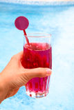 Female hand holding red cold drink at the pool Stock Images