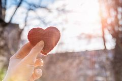 A female hand holding a red heart. A female hand is holding a bright red knitted heart against morning dawn urban landscape background. The concept of family royalty free stock photos
