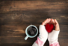 Female hand holding red heart with hot cup of coffee royalty free stock photos