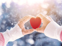 Female hand holding red heart. Up to the sun during morning with a snow in winter - love and valentine concept, soft focus technique royalty free stock photos