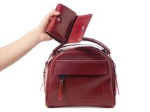 Female hand holding red purse and red bag. On white background isolation Stock Photos