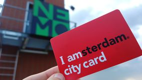 Female hand holding a red tourist guest card `I Amsterdam` on the background of signs of the Nemo Museum. Card for museums. And public transport royalty free stock photo