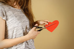 Female hand holding red Valentines card with heart on b. Ackground. Ð¡ut with scissors royalty free stock image