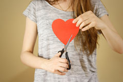 Female hand holding red Valentines card with heart on b. Ackground. Ð¡ut with scissors royalty free stock photo