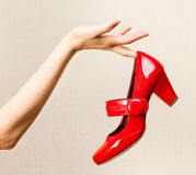 Female hand holding red varnish shoes on a high heel. Stock Photo