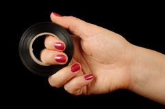 Female hand holding roll of duct tape isolated on the black background Stock Images