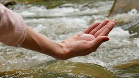 Female Hand Holding A Rose Quartz Crystal Yoni Egg On River