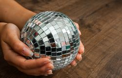 Female hand holding a shiny silver mirror disco ball on wooden background. Royalty Free Stock Photo