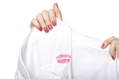 Female Hand Holding Shirt With Lipstick Mark Stock Photo