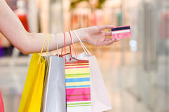 Female hand holding shopping bags and credit card Royalty Free Stock Photo