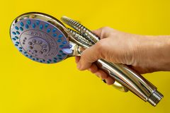 Female hand holding shower head and flexible hose on a yellow background. Handheld shower head with with function switch. Modern shower equipment. Plumbing stock photos