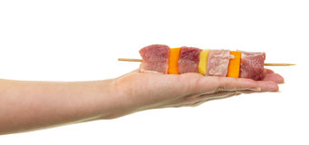 Female hand holding  skewer with slices  raw meat and vegetables. Female hand holding a skewer with slices of raw meat and vegetables isolated on white Royalty Free Stock Photography