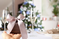 Female hand holding small elegant gift with ribbon. royalty free stock photography