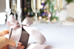 Female hand holding small elegant gift with ribbon. stock photos