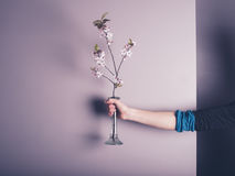 Female hand holding small vase with flowers. A female hand is holding a small vase with some pink flowers in it Royalty Free Stock Image